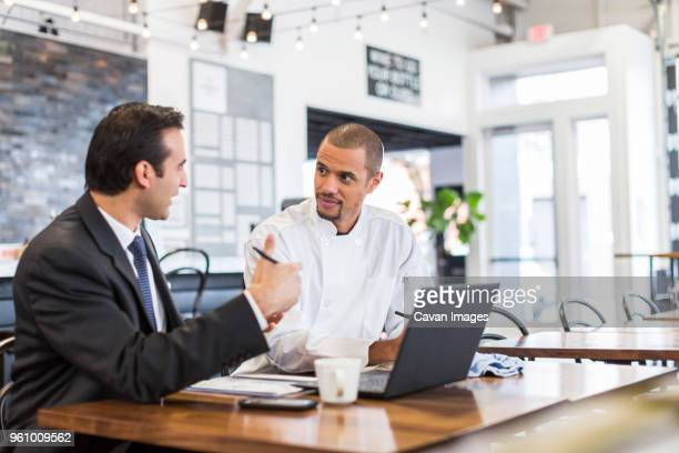 Businessman explaining with male chef in restaurant