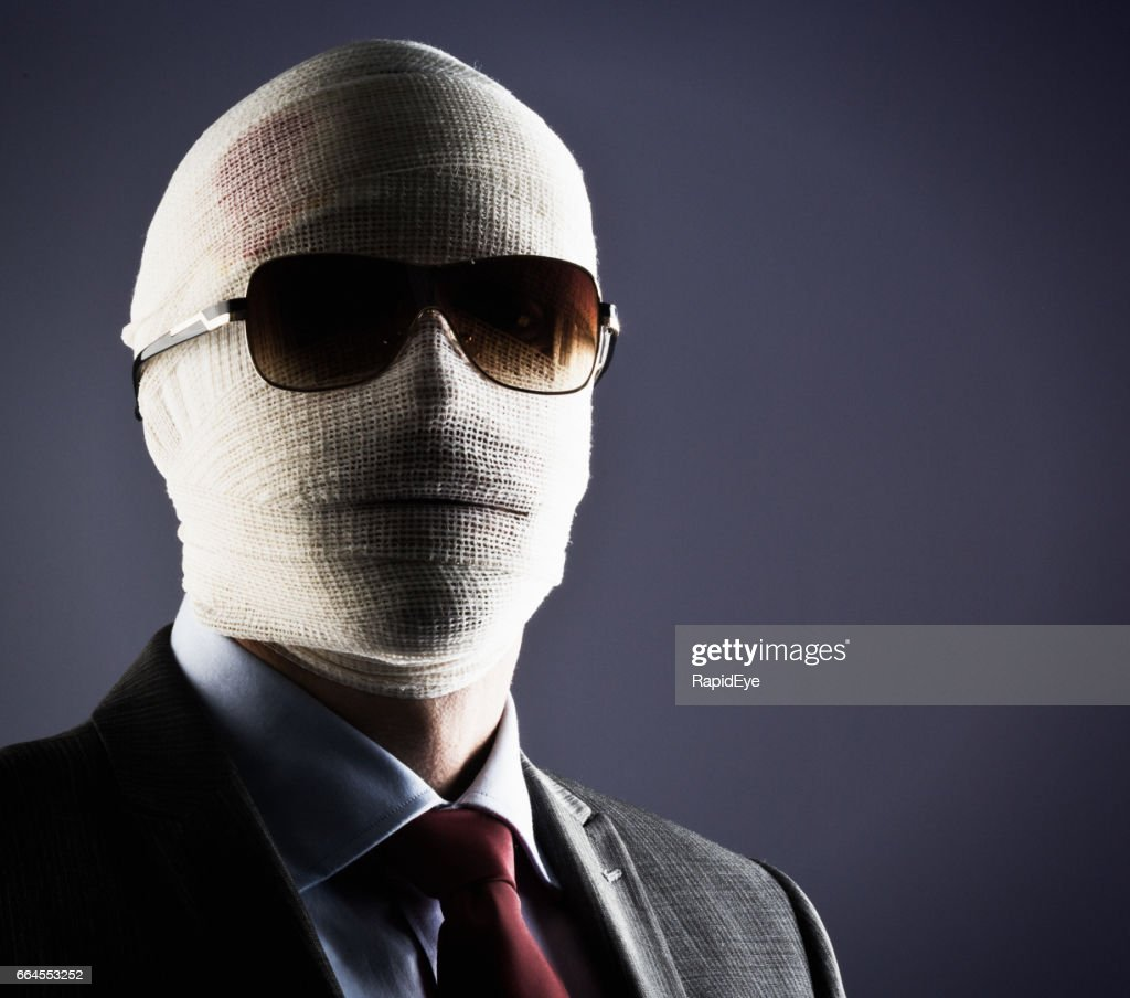 Businessman, face obscured by bandages and sunglasses, gives challenging stare : Stock Photo