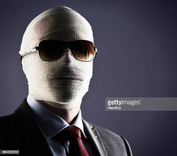 Businessman, face obscured by bandages and sunglasses, gives challenging stare