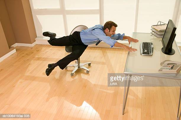 Businessman falling from chair, laughing, elevated view