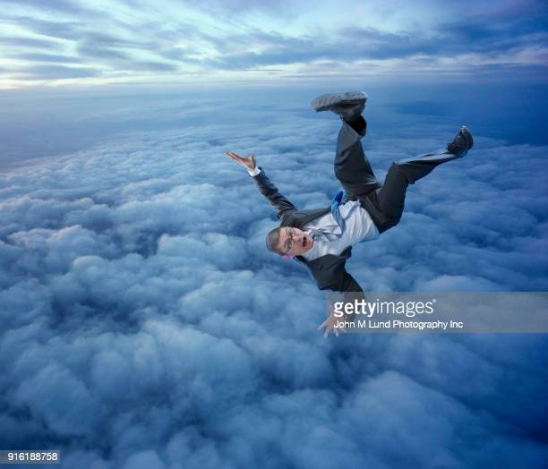 businessman falling in clouds - falling stock pictures, royalty-free photos & images