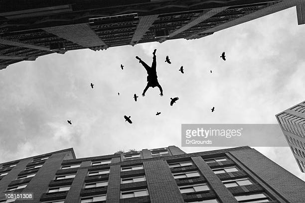 businessman falling off office building roof with birds flying - suicide stock photos and pictures