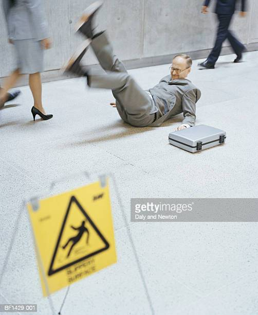 businessman falling over, legs in air (blurred motion) - clumsy stockfoto's en -beelden