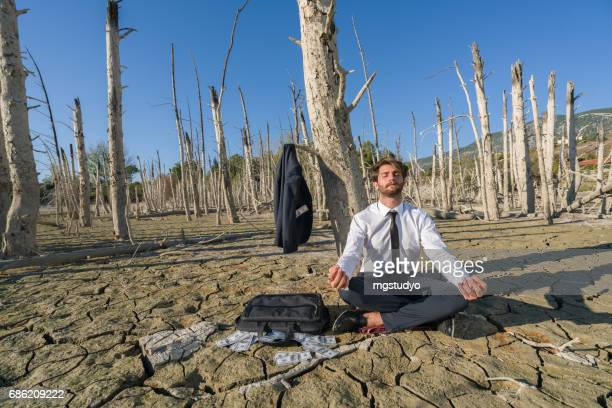 Businessman ,fashion model resting  on cracked earth
