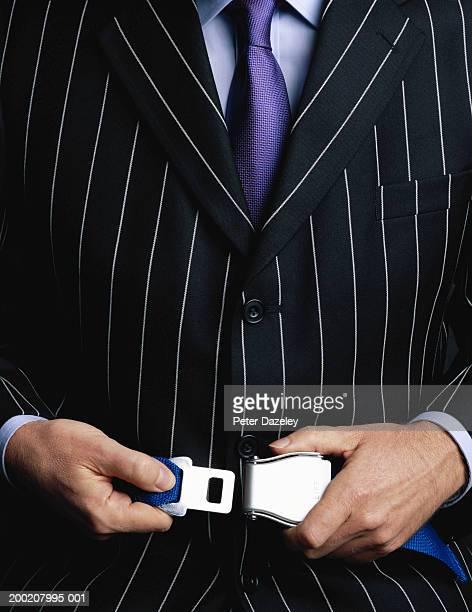 Businessman fastening seatbelt, close-up