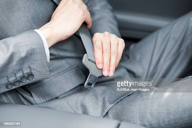 Businessman fastening the seat belt