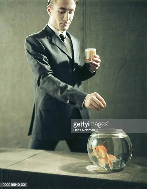 Businessman feeding goldfish