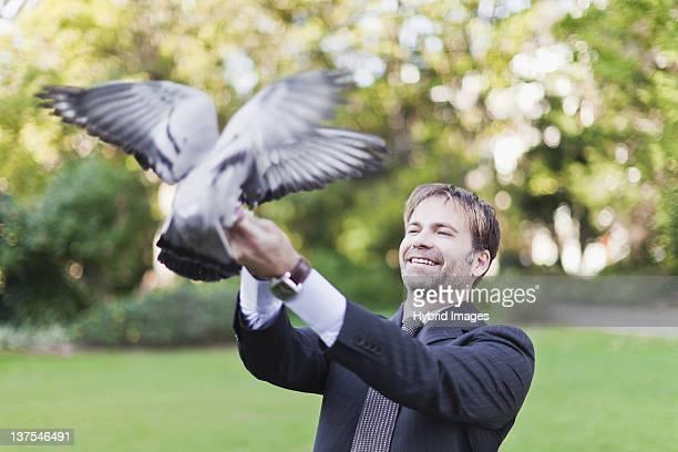 Businessman feeding pigeons in park