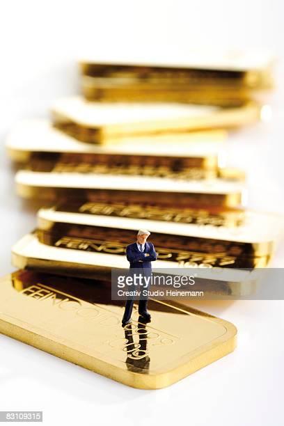 businessman figurine and gold bars - geld und finanzen stock-fotos und bilder