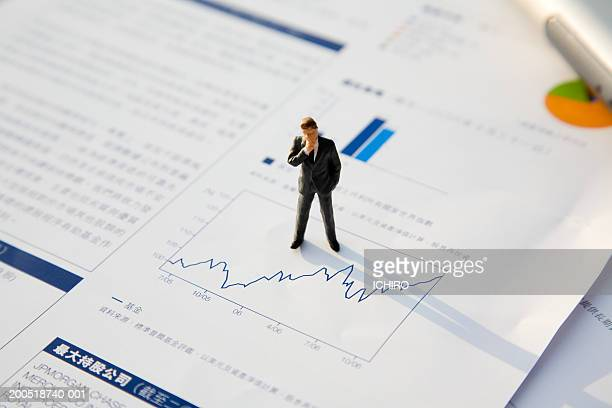 Businessman figurine atop line graph, elevated view