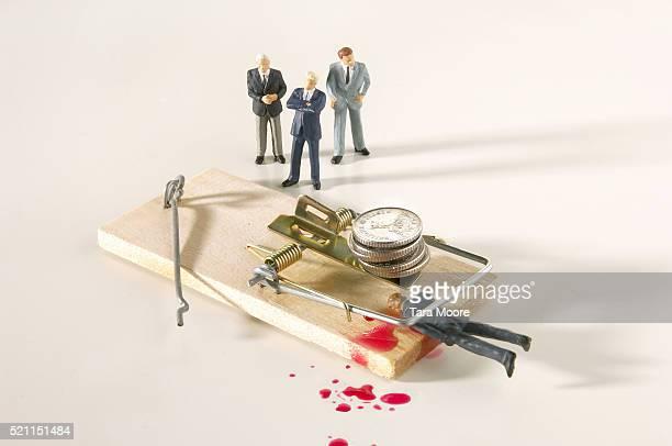 Businessman Figurine Caught in Mousetrap