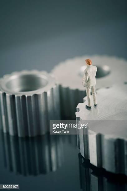 Businessman figurine cheeking on networking gears, close-up.