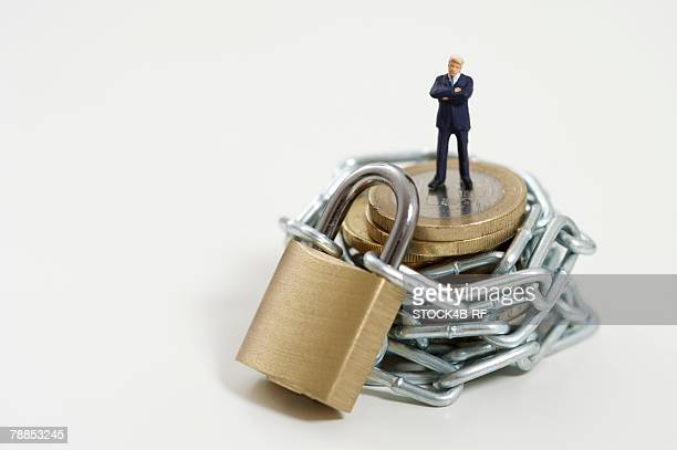 Businessman figurine on a stack of coins wrapped of a chain with a padlock