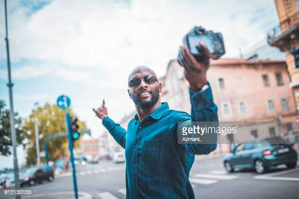businessman filming a vlog - pointing at camera stock photos and pictures