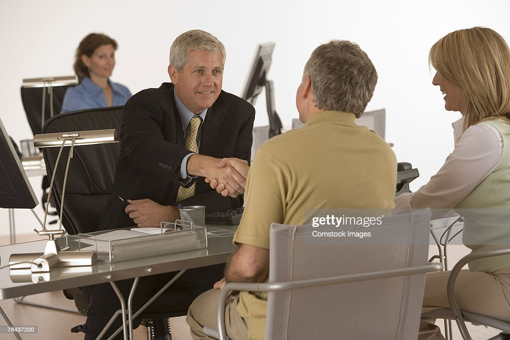 Businessman finsihing an agreement with couple : Stockfoto
