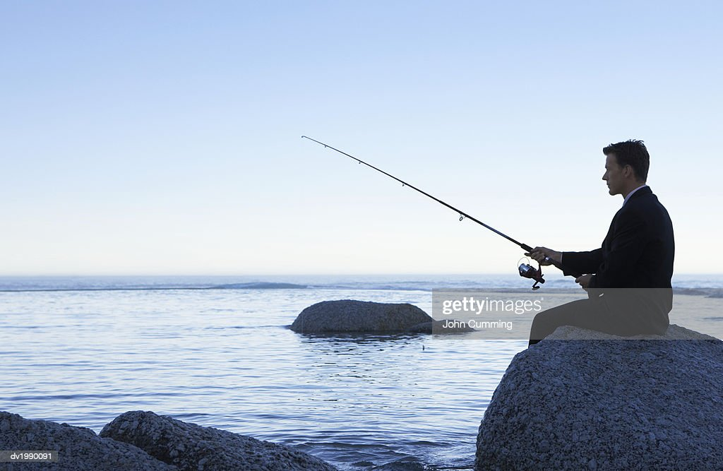 Businessman Fishing from a Rock : Stock Photo