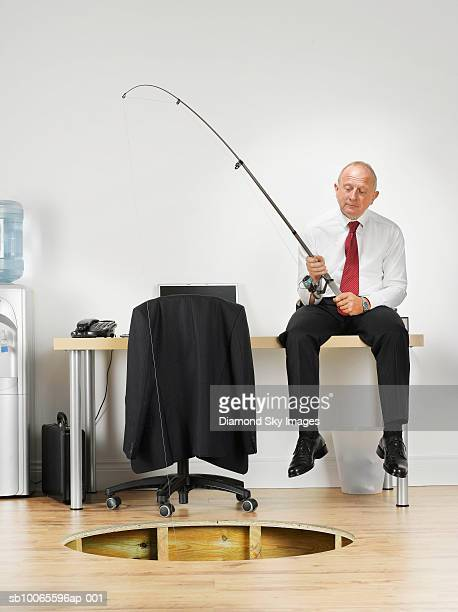 Businessman fishing in hole of wooden floor in office