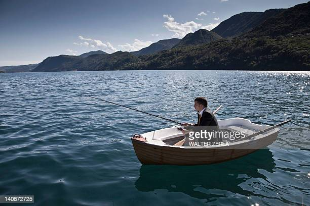Businessman fishing in rowboat