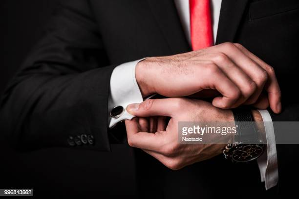 businessman fixing cuff links - masculinity stock pictures, royalty-free photos & images