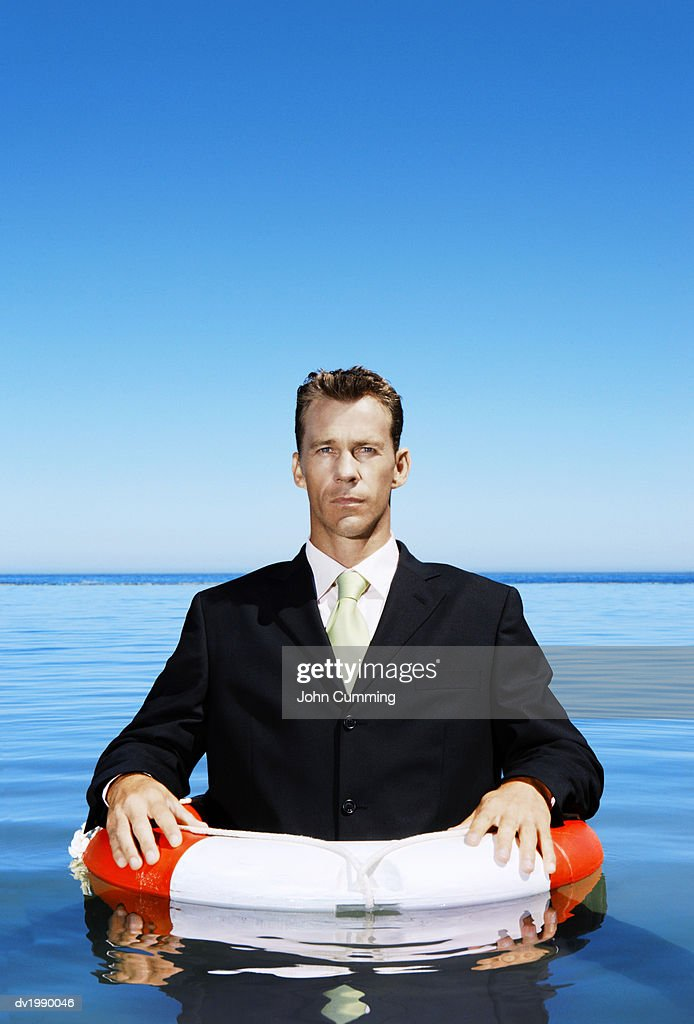 Businessman Floating in the Sea with a Rubber Ring : Stock Photo