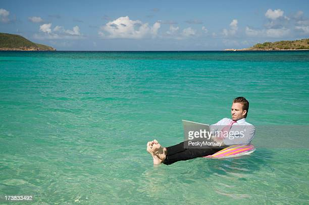 ビジネスマン浮かぶ屋外のトロピカルな海のラップトップで仕事する