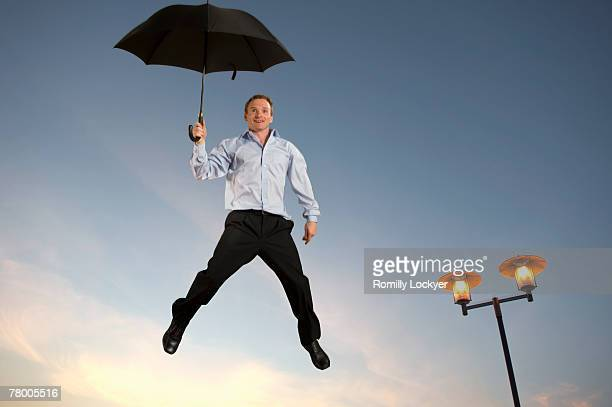 Businessman floating with an umbrella