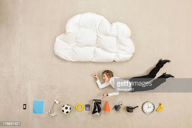 Businessman flying between cloud shape pillow and variety of items
