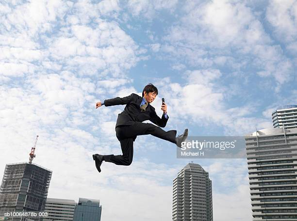 Businessman flying in air, holding mobile phone, low angle view