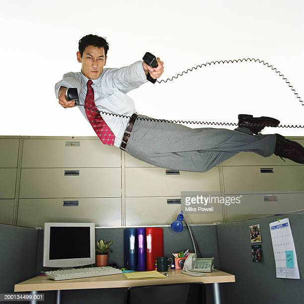 Businessman flying over desk, holding telephone receivers