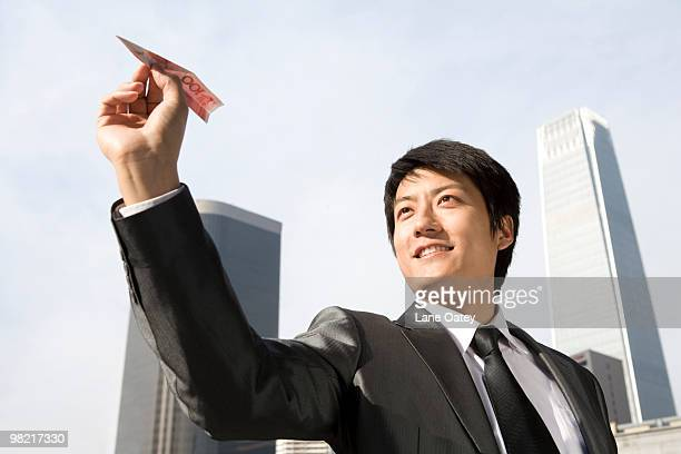 Businessman Flying RMB Paper Airplane