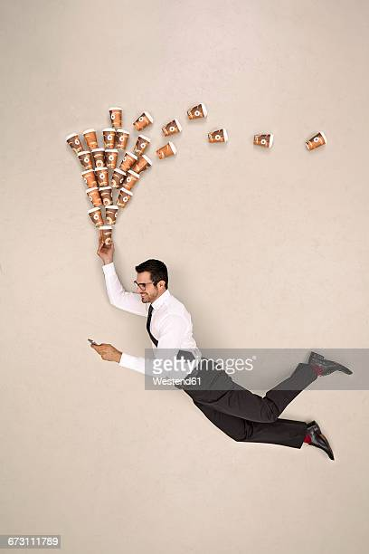 Businessman flying with coffee while looking at smartphone