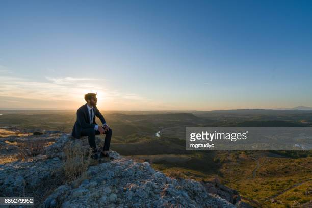 Businessman freedom on the top of a high mountain