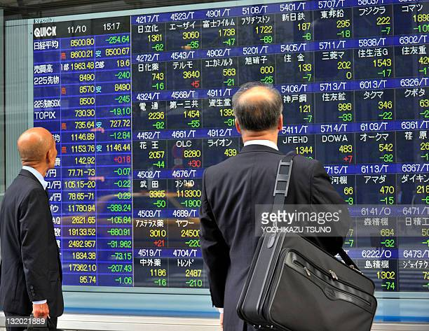 Businessman gaze at a share prices board in Tokyo on November 10 2011 Japan's share prices lost 25464 points to close at 850080 points at the Tokyo...
