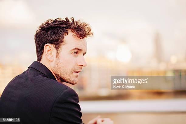 Businessman gazing from Thames riverside, London, UK