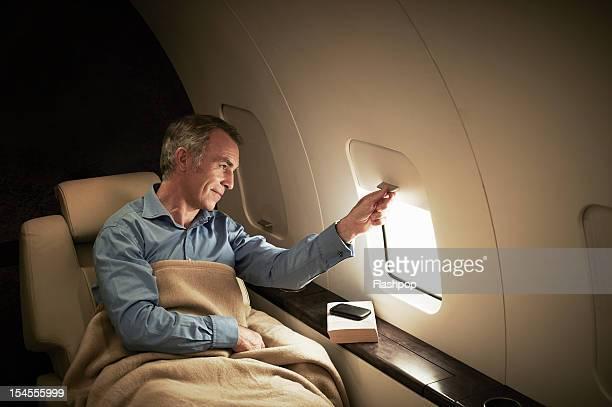 Businessman gazing out of window aboard flight