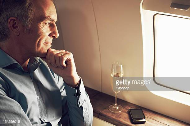 businessman gazing out of window aboard flight - millionnaire stock photos and pictures