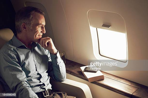 businessman gazing out of window aboard flight - capital stock pictures, royalty-free photos & images