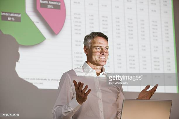Businessman gesturing and giving slide presentation