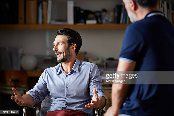 businessman gesturing while discussing in office - esprimere a gesti foto e immagini stock