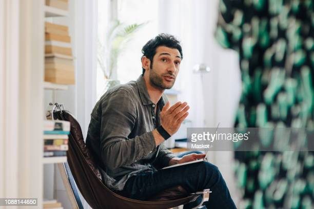 businessman gesturing while discussing with coworker in meeting at home office - gesturing stock pictures, royalty-free photos & images