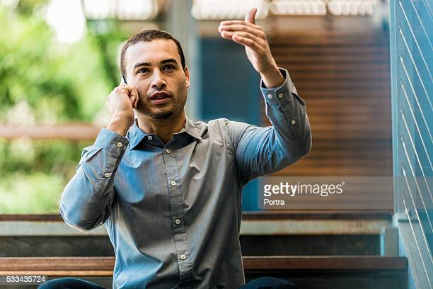 Businessman gesturing while using mobile phone