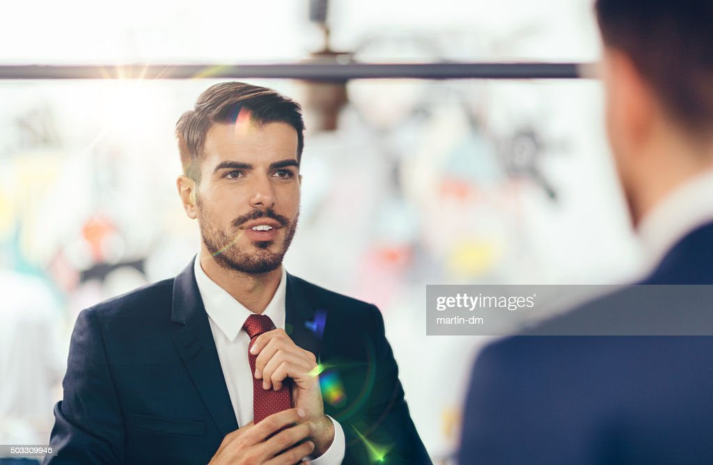 Businessman getting dressed in front of the mirror : Stock Photo