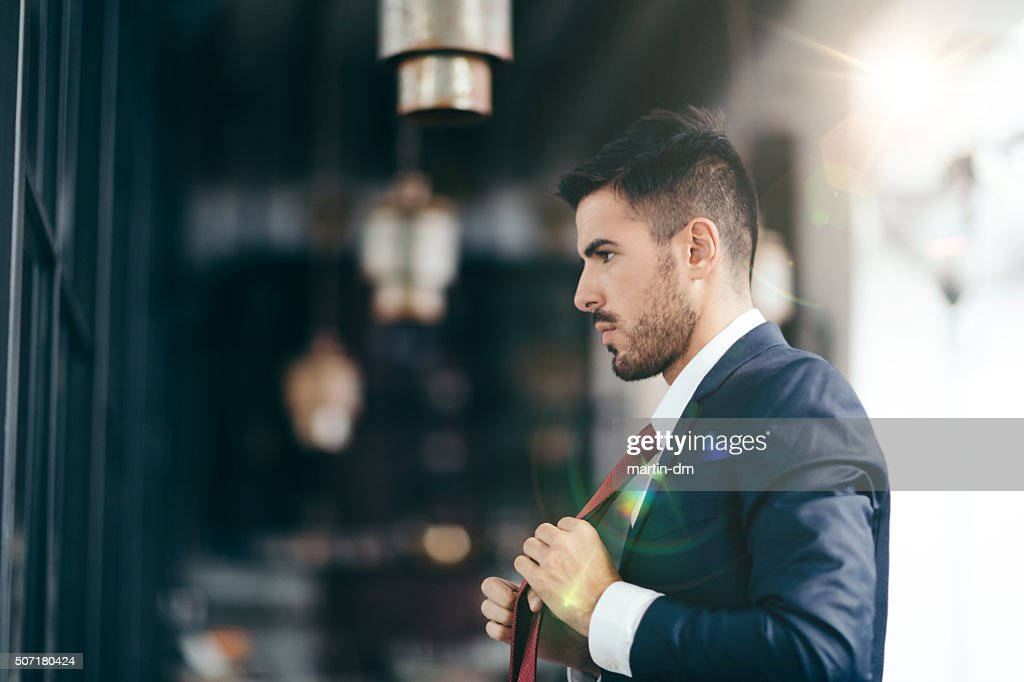 Businessman getting dressed in front of the mirror : Stockfoto