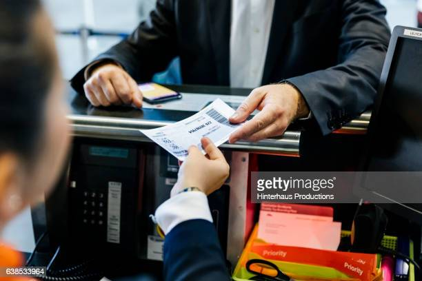 Businessman getting his boarding pass at check-in counter