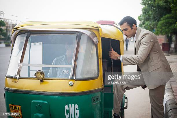 businessman getting into an auto rickshaw - rickshaw stock pictures, royalty-free photos & images