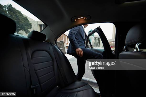 Businessman getting into backseat of exclusive cab