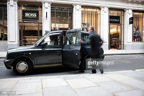 Geschäftsmann beim Aufrufen taxi vor Mode-store