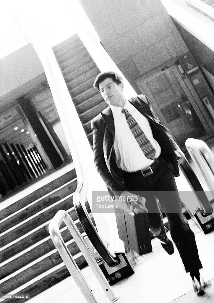 Businessman getting off escalator, holding briefcase, blurred, b&w. : Stockfoto