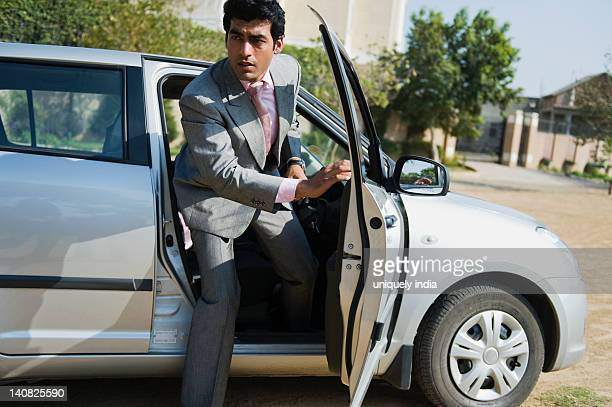 Businessman getting out of a car, Gurgaon, Haryana, India