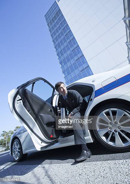 Businessman getting out of taxi